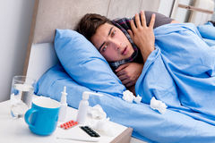 The sick ill man in the bed taking medicines and drugs Royalty Free Stock Images