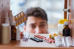 The sick ill man looking for medicines at farmacy shelf. Sick ill man looking for medicines at farmacy shelf Stock Photography