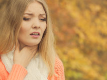 Sick ill woman in autumn park. Royalty Free Stock Image