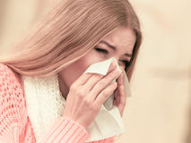 Sick ill woman in autumn park sneezing in tissue. Royalty Free Stock Photography