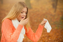 Sick ill woman in autumn park sneezing in tissue. Royalty Free Stock Photo