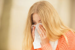 Sick ill woman in autumn park sneezing in tissue. Stock Image