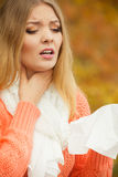 Sick ill woman in autumn park sneezing in tissue. Stock Photo