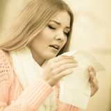 Sick ill woman in autumn park sneezing in tissue. Stock Photos