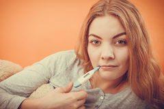 Sick ill woman with digital thermometer in mouth. Royalty Free Stock Image