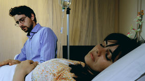 Sick ill woman sleeping in hospital while husband is reading. Man reading while waiting in hospital next to sick woman Stock Photography