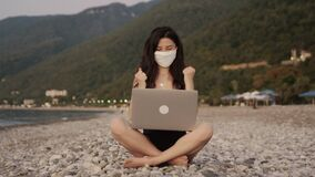 Pretty businesswoman in bikini in medical mask working on laptop alone by the sea at the beach during sunset. Freelance