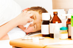 Sick kid boy with bad cold using paper napkins. Close-up portrait of sick kid boy with bad cold laying in bed and using paper napkins Stock Photo