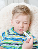 Sick kid with high fever laying in bed and mother checks the tem Royalty Free Stock Image