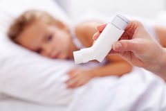 Sick kid with inhaler in foreground. Asthma or other respiratory illness Stock Images