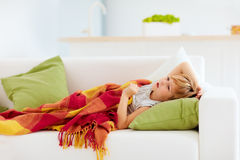 Sick kid with runny nose and fever heat lying on couch at home Royalty Free Stock Photography