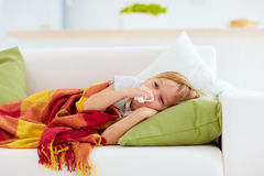 Sick kid with runny nose and fever heat lying on couch at home Stock Photo