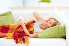 Sick kid with runny nose and fever heat lying on couch at home Stock Photos