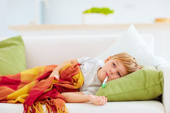 Sick kid with runny nose and fever heat lying on couch at home Stock Images
