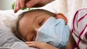 Sick kid with thermometer, ill child, mother nursing petting ill girl, children health care