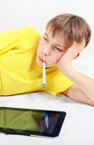 Sick Kid with Thermometer. Sick Kid with Tablet Computer and Thermometer on the Bed royalty free stock photo