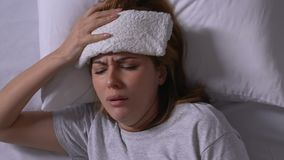 Sick lady with towel on forehead coughing in bed, low immune system, flu virus