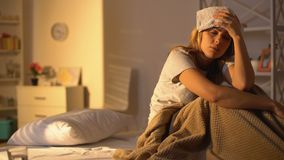 Sick lady with towel on forehead suffering from migraine, lying in bed at home. Stock footage stock video footage