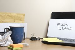 Sick leave message left on a messy office desk stock image