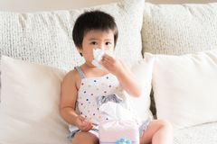 Sick little Asian girl wiping or cleaning nose with tissu. E sitting on sofa at home. Medicine and health care concept stock image