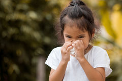 Sick little asian girl wiping or cleaning nose with tissue. On her hand Royalty Free Stock Image