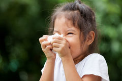 Sick little asian girl wiping or cleaning nose with tissue. On her hand Stock Image