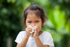 Sick little asian girl wiping or cleaning nose with tissue. On her hand Stock Photos