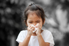 Sick little asian girl wiping or cleaning nose with tissue. On her hand on black and white background Royalty Free Stock Photos
