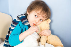 Sick little boy checking his body temperature Royalty Free Stock Images