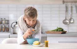 Sick little boy eating broth to cure cold at table. In kitchen stock photo