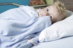 Sick little boy in a hospital bed Stock Images