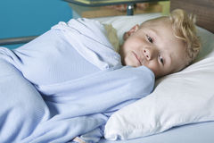 Sick little boy in a hospital bed Royalty Free Stock Photography