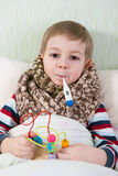 Sick little boy lying in bed with thermometer Royalty Free Stock Images