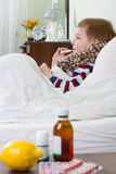 Sick little boy lying in bed with thermometer Stock Images