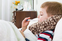 Sick little boy lying in bed with thermometer Stock Photos