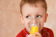 Sick little boy makes inhalation mask for breathing at home Royalty Free Stock Photo