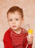 Sick little boy makes inhalation mask for breathing at home. Sick child makes himself inhalation mask for breathing at home Royalty Free Stock Photography