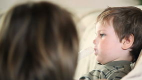 Sick little boy and mother using nebulizer to inhale the medicine panning, stock footage Royalty Free Stock Photography