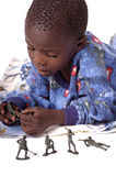 A sick little boy playing with army men Stock Images