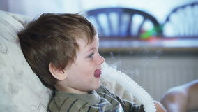 Sick little boy using nebulizer to inhale medicine, stock footage Stock Images