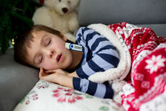Sick little child, boy, with high fever sleeping on the couch at Stock Photo