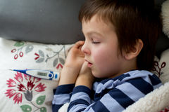Sick little child, boy, with high fever sleeping on the couch at Royalty Free Stock Images