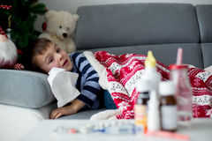 Sick little child, boy, with high fever sleeping on the couch at Stock Photography