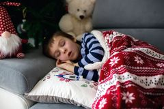 Sick little child, boy, with high fever sleeping on the couch at. Home, lots of medicine on the table Royalty Free Stock Photo