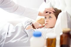 Sick little child with temperature in bed. Stock Photo