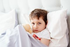 Sick little child with temperature in bed. Royalty Free Stock Photos