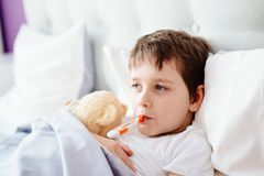 Sick little child with temperature in bed. Stock Photos