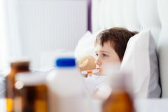 Sick little child with temperature in bed. Stock Images