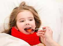 Sick little girl in bed taking medicine Stock Photos