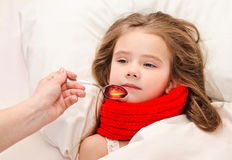 Sick little girl in bed taking medicine Royalty Free Stock Images